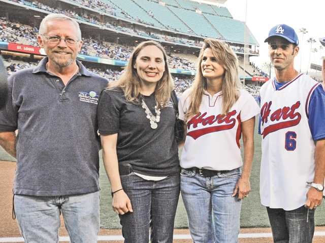 From left, Pat Downing of the Santa Clarita Arts & Events Office, Holly Michaels of the Santa Clarita Recreation Division, and Maggie Blaha and Ron Marone of Hart Baseball and Softball are introduced as part of Santa Clarita Dodger Day festivities at Dodger Stadium in Los Angeles on Saturday.