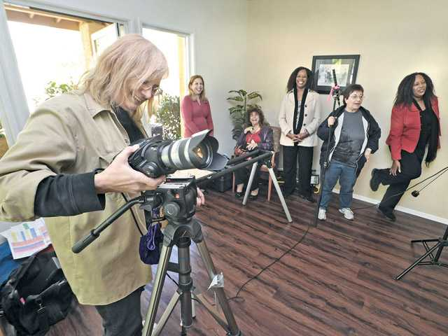Nancy Hanks, left, prepares the camera as the members of dollHouse Productions prepare to record a scene in the card room at Valley Oaks Village in Newhall on Saturday.
