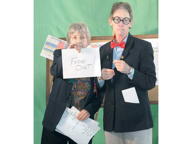 "Actors Rachel Arno, left, as ""the announcer"" and Sue Upperco as ""Marvin"" hold the final card as they perform for the camera in skit about storyboarding a movie."