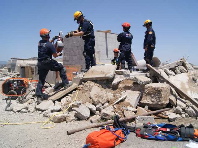 Members of the California Task Force 2 Urban Search and Rescue Team use a circular saw to break up concrete at a training exercise near Val Verde on Sunday.