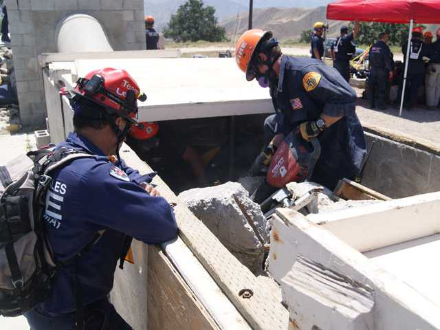 Members of the California Task Force 2 Urban Search and Rescue Team use a jackhammer to break up concrete at a training exercise near Val Verde on Sunday.