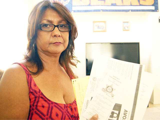 Hortensia Mares holds the paperwork required to replace her stolen purse at her daughter's home in Lancaster on Monday.