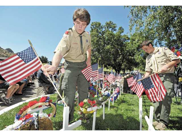 Brothers Joey Prata, left, and Trevor Prata, both of Boy Scout Troop 303, place American flags on grave markers during the Memorial Day tribute at Eternal Valley Memorial Park in Newhall last year.