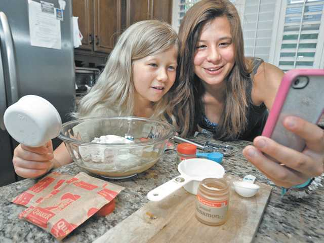 Taylor McLaughlin, 9, left, and sister Juliet Morales, 17, a junior at William S. Hart High School, check online for the recipe for pumpkin spice cookies. Morales is raising funds by selling cookies for an Arthritis Walk fundraiser.