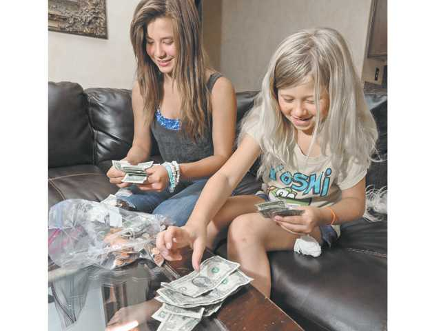 Juliet, left, and sister Taylor count the nearly $800 raised  from Hart High cookie sale fundraiser for the Arthritis Walk.