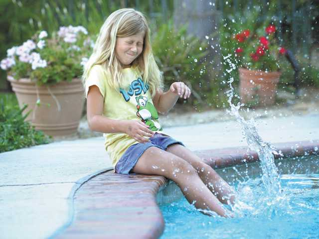 Taylor, 9, splashes in the backyard pool at her Stevenson Ranch home.