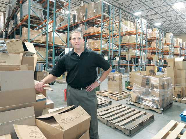Mike Klepfer, executive vice president of operations for AMS Fulfillment, stands in the company's Valencia warehouse on Thursday.