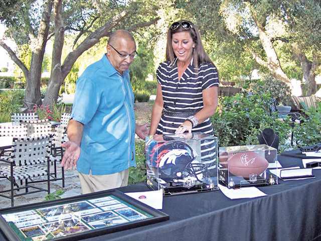 Jim Ventress, left, chief professional officer of the Boys & Girls Club of Santa Clarita Valley, and Ronda Chobanian, director of development of the club, view a few of the live auction items that will be up for bid at Saturday's auction.