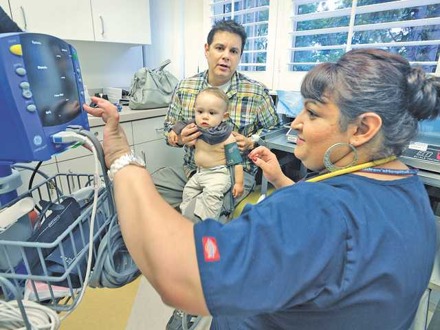 Julian Andrade holds his 10-month-old son Matias as medical assistant Annalise D'Souza checks the boy's vital signs in an examination room at Children's Hospital Los Angeles' Valencia Clinic on Friday.
