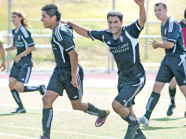 Santa Clarita Storm players Andres Bueno, left, and Martin Galvan celebrate after Bueno scores a goal against the Bay Area Ambassadors on Saturday at Hart High.