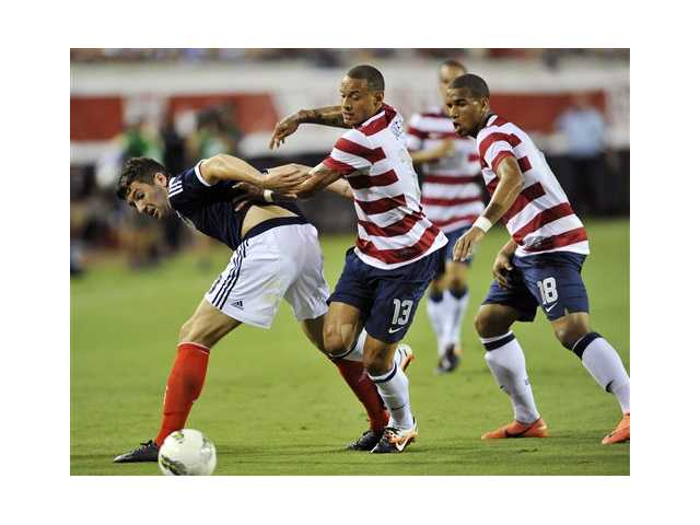 United States' Jermaine Jones (13) and Terrence Boyd (18) battle Scotland's Charlie Mulgrew for the ball during an exhibition soccer match, Saturday, May 26, 2012, in Jacksonville, Fla. United States won 5-1.