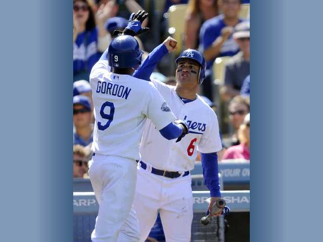 Dodgers infielder Dee Gordon (9) celebrates with teammate Jerry Hairston Jr. (6) after scoring on a Tony Gwynn single to center in the eighth inning against the Astros on Sunday in Los Angeles.