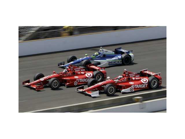 Dario Franchitti, center, of Scotland, leads teammate Scott Dixon, bottom, of New Zealand, and Tony Kanaan, top, of Brazil, to the finish line on the final lap of IndyCar's Indianapolis 500 auto race at Indianapolis Motor Speedway in Indianapolis