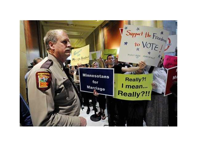 A state trooper stands by as demonstrators on both sides of the gay marriage issue gather outside the Minnesota House in St. Paul, Minn. Poll after poll shows public support for same-sex marriage steadily increasing, to the point where it's now a majority viewpoint.