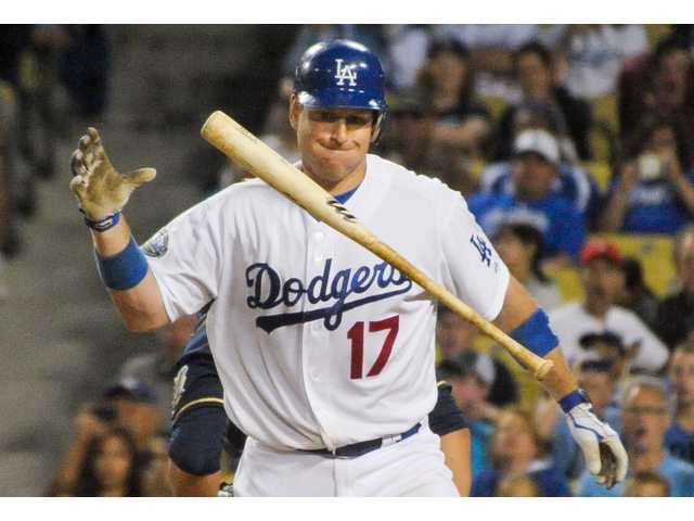 Dodgers catcher A.J. Ellis flips his bat in frustration after striking out against the Brewers during the eighth inning on Monday in Los Angeles.