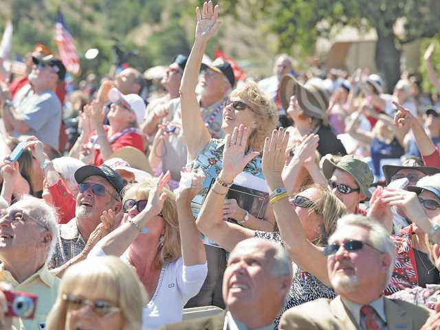 Attendees of the Memorial Day Tribute wave to passing aircraft in Newhall on Monday.