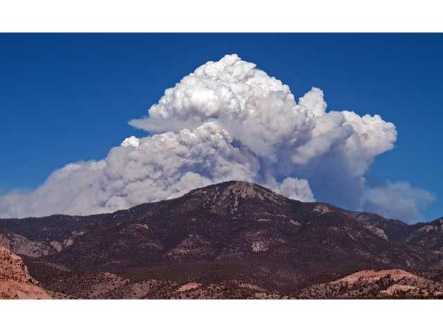 A plume of smoke rising from the Whitewater fire burning in the Gila Wilderness east of Glenwood, N.M. Fire managers said the blaze had charred more than 10,000 acres before merging Wednesday afternoon with the nearby 11,500-acre Baldy fire.