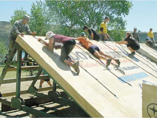Racers pull themselves up and over a steep wall on the mud run course at Castaic Lake.