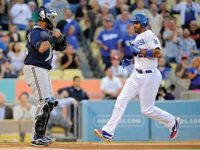 Los Angeles Dodgers' Matt Kemp, right, scores on a double by Andre Ethier as Milwaukee Brewers catcher Martin Maldonado looks on during the first inning of their baseball game on Wednesday in Los Angeles. Kemp returned to the disabled list after injuring a hamstring injury.