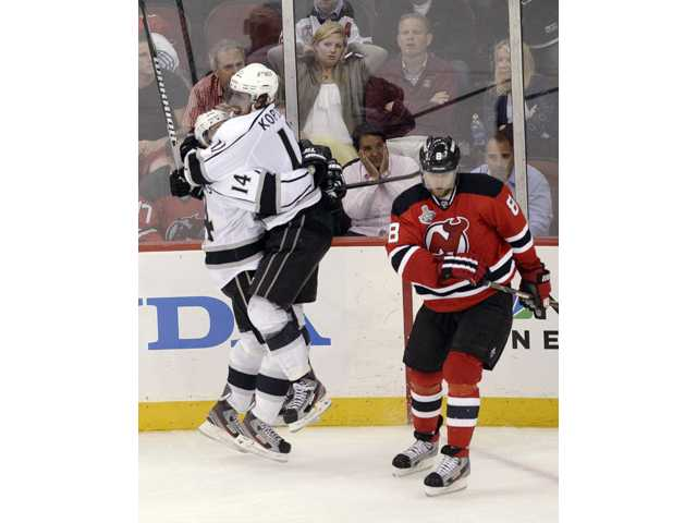 Los Angeles Kings' Anze Kopitar (11) celebrates with teammate Justin Williams after scoring in overtime during Game 1 of the Stanley Cup finals, as New Jersey Devils' Dainius Zubrus (8) skates away Wednesday in Newark, N.J.