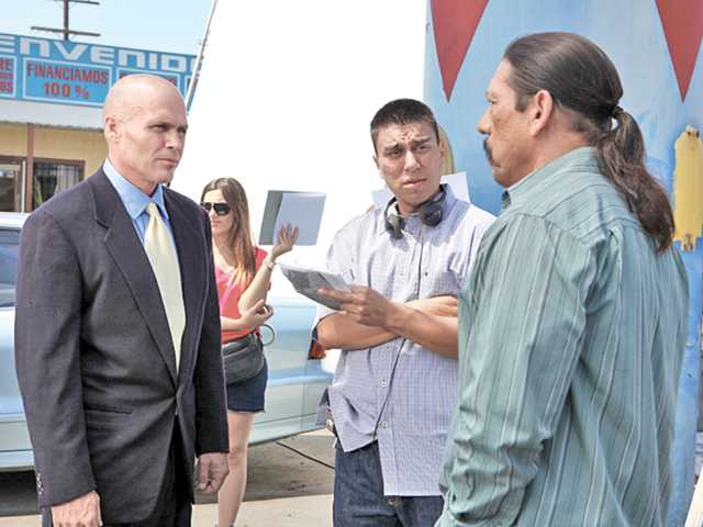 Director Nick Parada, center, works with actors Harris James Maynard, left, and Danny Trejo, right. In this scene, the character Gilbert, played by Trejo, is trying to find the whereabouts of his underage niece Danielle, played by Alexandra Mason.