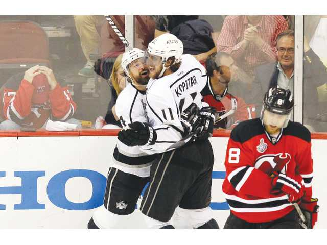 Los Angeles King Anze Kopitar (11) celebrates with teammate Justin Williams after scoring the game-winning goal in Game 1 of the Stanley Cup finals on Wednesday in Newark, N.J.