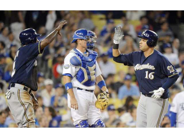 Milwaukee Brewer Aramis Ramirez, right, is congratulated by teammate Nyjer Morgan, left, as Los Angeles Dodgers catcher A.J. Ellis looks on Thursday in Los Angeles.