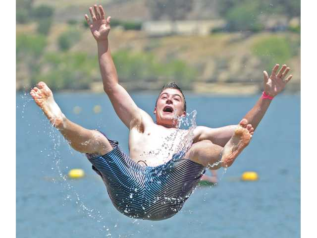 Castaic Middle School eighth-grader Trevor Hendrickson is tossed into the air by fellow students as they celebrate the class' promotion to high school during their celebration at the lake on Friday.