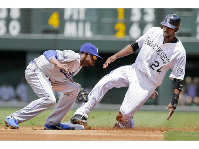 Rockies outfielder Dexter Fowler (24) steals second base with Dodgers shortstop Dee Gordon covering during the first inning on Sunday in Denver.