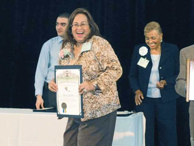 Tess Carlos, a 16-year volunteer with the SCV Senior Center, is presented her award by commissioners from the Los Angeles County Commission on Aging at the 47th annual Older Americans Recognition Day Awards.