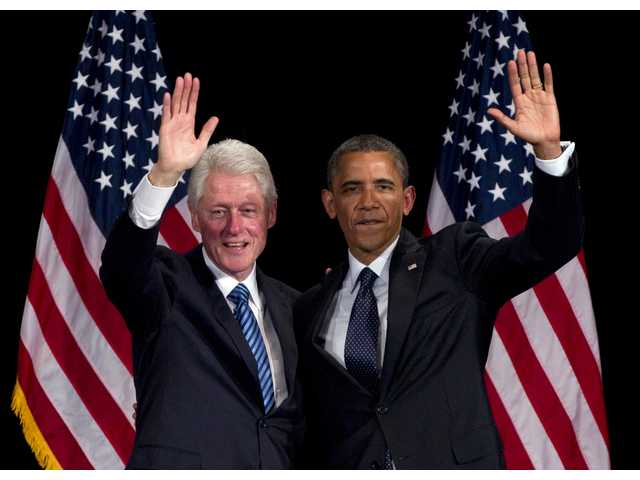Former President Bill Clinton and President Barack Obama wave to the crowd during a campaign event at the Waldorf Astoria on Monday.