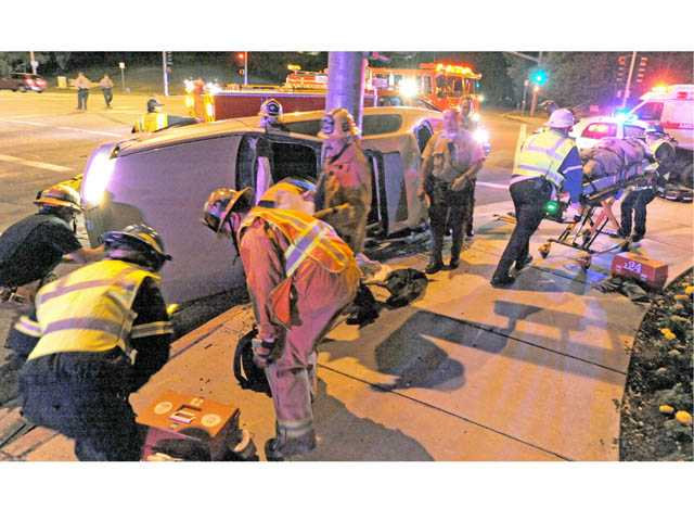 Emergency medical technicians, right, transport a 24-year-old man to an ambulance after he is rescued from a Toyota Camry on its side at the intersection of Rockwell Canyon Road and McBean Parkway in Valencia on Tuesday night.