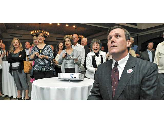 Scott Wilk joins supporters in watching early returns projected on a screen at the Hyatt Regency Valencia on Tuesday.