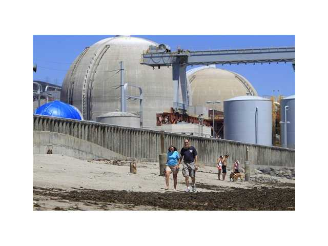 Beach-goers walk on the sand near the San Onofre nuclear power plant in San Clemente.