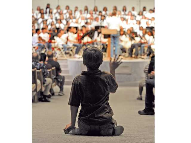 Scotty Gregory, 9, waves to a friend in the chours as he sits in the aisle with the audience during a performance.