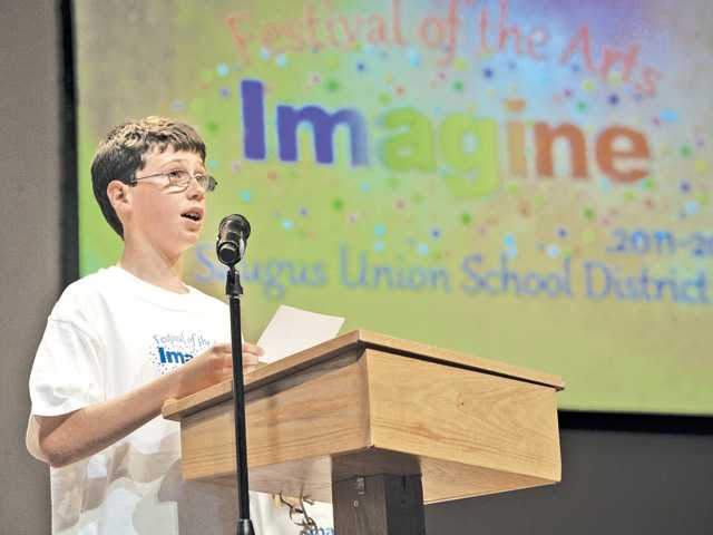 "Emblem Elementray School student Connor Modugno reads the poem he wrote to the theme, ""Imagine"" at the Saugus Union District's Festival of the Arts held at Grace Baptist Church in Santa Clarita recently."