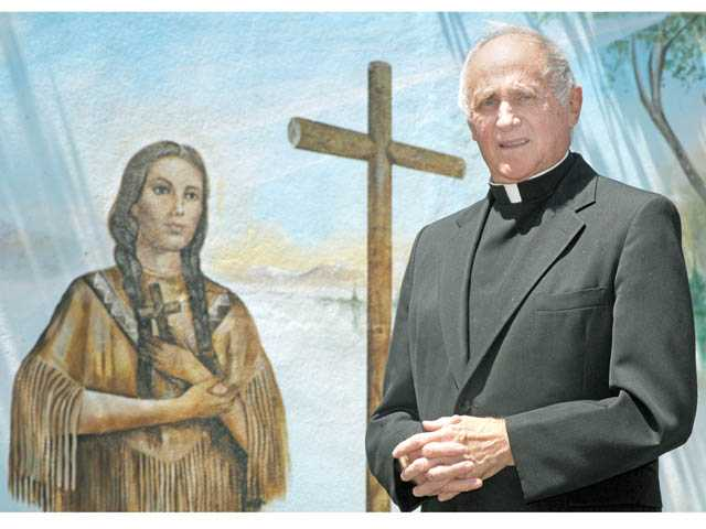Monsignor Mike Slattery with a mural of Kateri Tekakwitha at Blessed Kateri Tekakwitha Catholic Church.