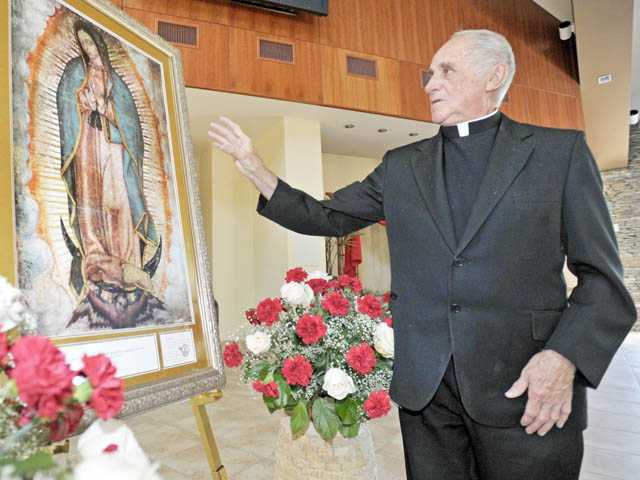 Monsignor Mike Slattery with a painting of Our Lady of Guadalupe.