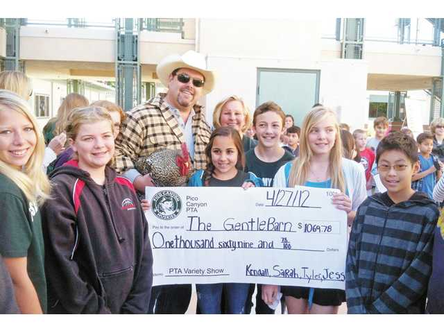 Pico Canyon Elementary School Variety Show emcees, left to right, Kendall Fortner, Sarah Kouchak, Tyler Allen and Jessica Judy present check of $1,069.78 raised from the show to The Gentle Barn President Jay Weiner.