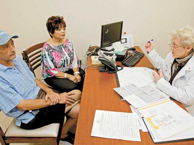 In this photo taken May 16, Dr. Pamela Sutton, right, talks to patient Carol Delzatto, center, and her husband, Paul Delzatto, at Broward General Hospital in Fort Lauderdale, Fla.