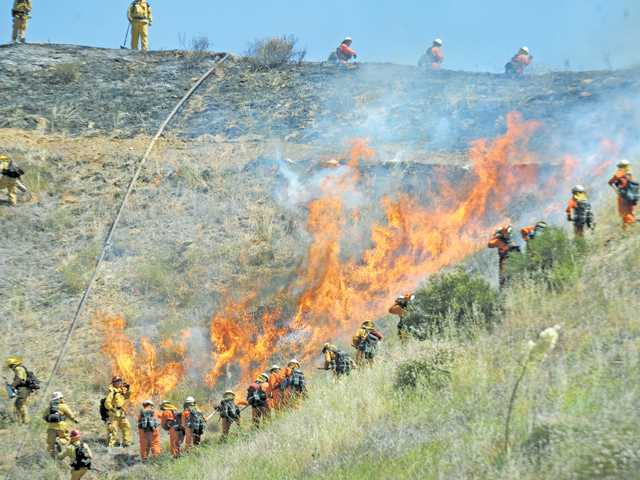 Firefighters and hand crews surround a controlled burn during a drill at Pitchess Detention Center in Castaic recently.