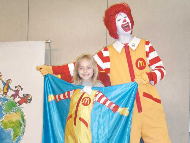 Ronald McDonald transforms Golden Oak Elementary School third-grader Hannah Jeppesen into a hero with the help of his magic cape. Ronald McDonald visited the school earlier this month to present students with a new show that demonstrates the importance of helping others.