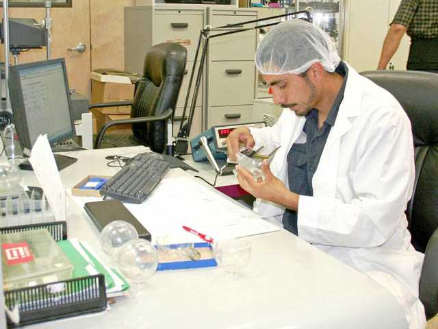 An employee works inside the quality-control department at Canyon Plastics, Inc.