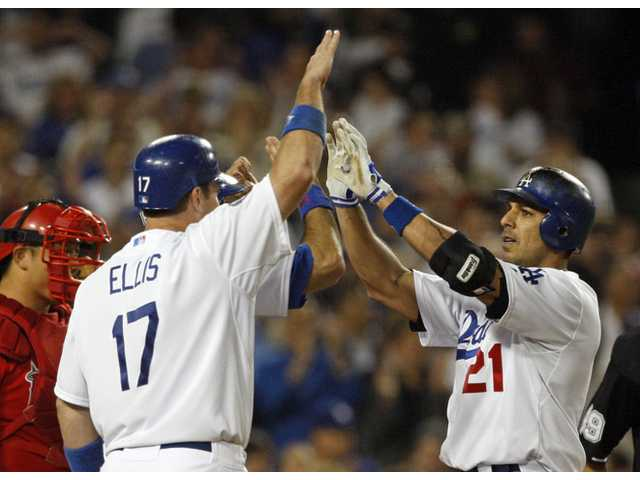 Los Angeles Dodger Juan Rivera, right, is greeted at the plate by A.J. Ellis and Andre Ethier, hidden behind Ellis, as all score on Rivera's home run against the Los Angeles Angels in the eighth inning in Los Angeles on Tuesday.