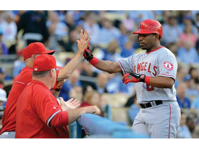 Los Angeles Angel Alberto Callaspo, right, is congratulated by coach Rob Picciolo, left, and manager Mike Scioscia after hitting a solo home run during the second inning against the Los Angeles Dodgers on Wednesday in Los Angeles.
