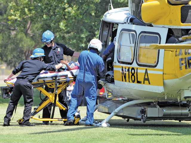 Paramedics load an 8-year-old girl into a Los Angeles County Fire helicopter at Central Park in Saugus to be transported to a hospital after she received a head injury on Wednesday afternoon.