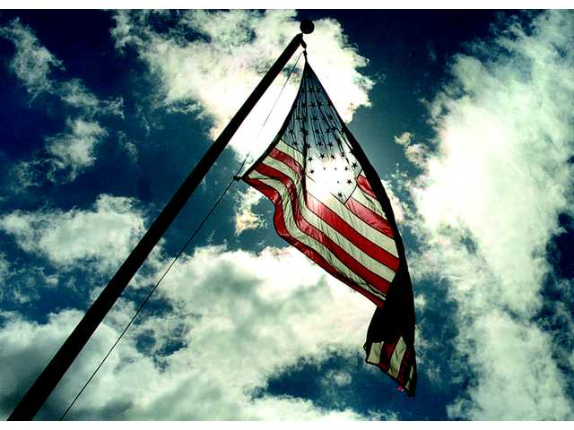 The sun peeks through the clouds on a blustery day as the flag flies over Central Park in Saugus on Wednesday.