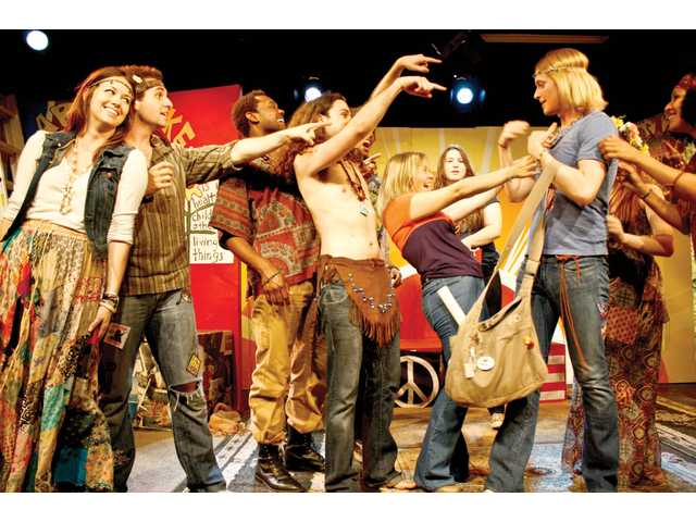 "Here, Claude, played by Christopher Chase (blonde at right with headband), ""returns"" to his hippie group."