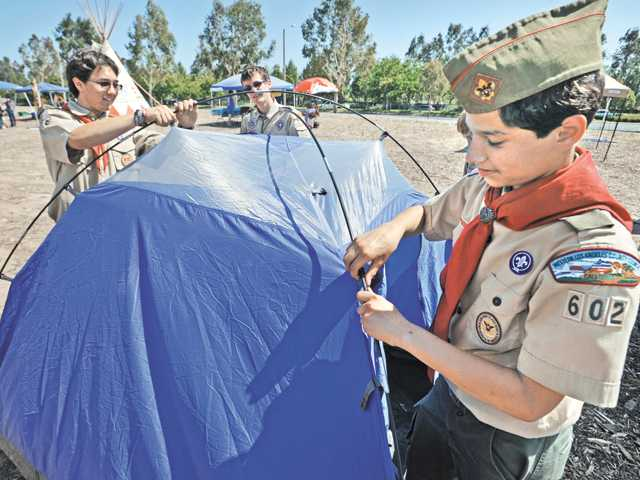 Boy Scouts from Troop 602, Valencia from left, James Kuba, 17, David Stotler, 17, and Ian Werner, 13, tear down their four-man tent at the Hart District Scout Expo 2012 held in the Bridgeport Marketplace Parking lot in Valencia on June 2.
