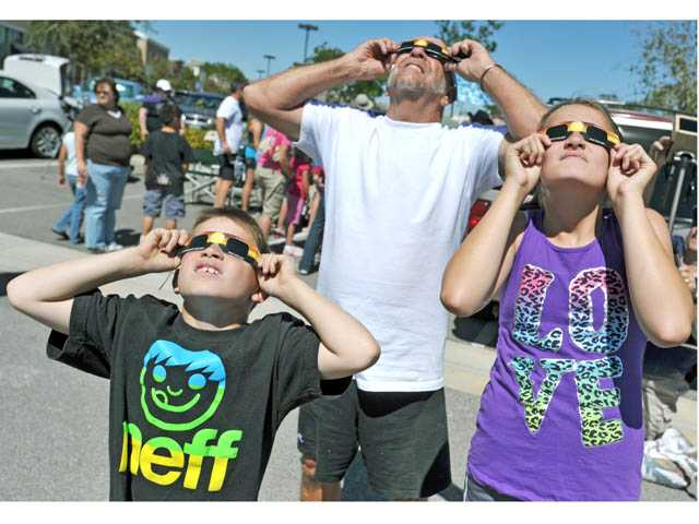 "Santa Clarita residents, from left, Jake Priske, Tom Culberhouse and Kaycie Priske look at the Transit of Venus through special glasses on the parking lot outside Babies ""R"" Us on Carl Boyer Drive in Santa Clarita on June 5."